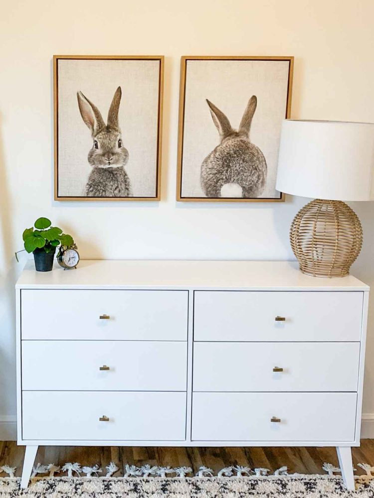 A white dresser with bunny art decals.